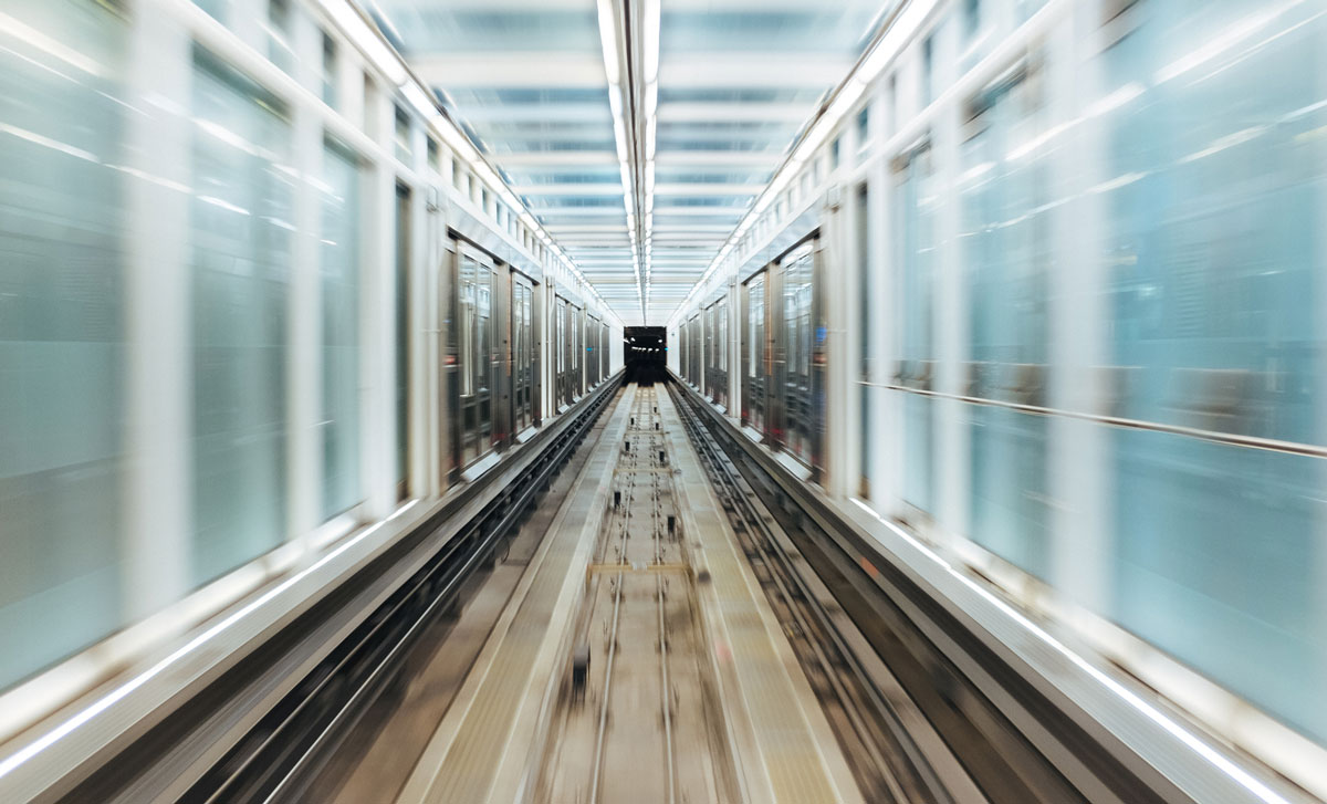Train travelling fast through tunnel with glass walls